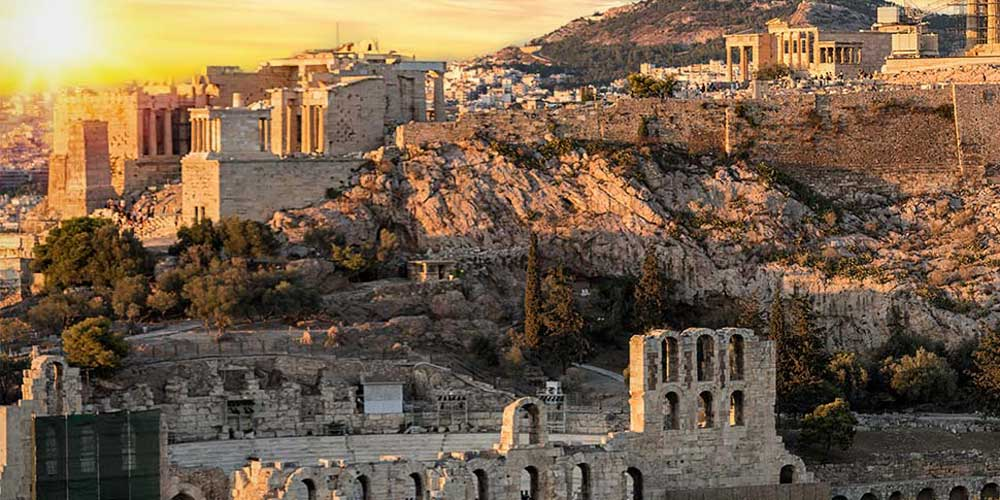 Sunset shining over the ruins of the Acropolis in Greece. Mars hill appears to be partially cut into the foundational rock.